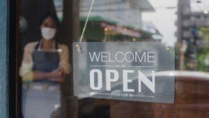 employee in store window wearing mask