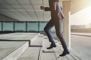 Businessman running up steps